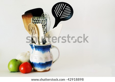 An assortment of used kitchen utensils stuffed into an old fashioned stone ware pitcher. Includes an apple, tomatoe and onion alongside pitcher. - stock photo