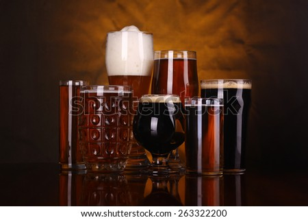 An assortment of various beer glass shapes and styles on a wooden table with a drapery in the background Stock photo ©
