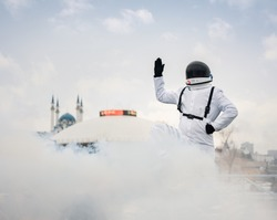 An astronaut in a spacesuit raised his hand up and greets earthlings against the background of the circus building and the Kul-Sharif mosque in Kazan,Russia.The astronaut is exploring the planet Earth
