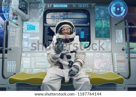 An astronaut sitting on the space shuttle uses the phone and some futuristic graphics appear around it. Concept of: holography, future, astronaut