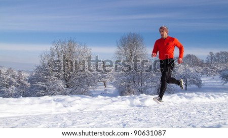 An athlete is jogging in a snowy landscape