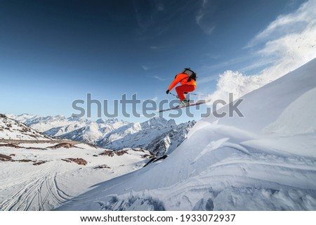 An athlete male skier jumps from a snow-covered slope against the backdrop of a mountain landscape of snow-covered mountains on a sunny day. The concept of winter sports.