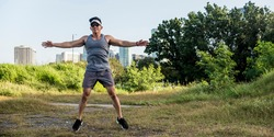 An athletic asian guy does jumping jacks at a open field near the city. Cardiovascular fitness. Working out outdoors.
