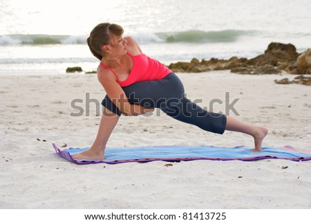 an athletic brown haired woman is doing yoga exercise bound extended side angle pose on an empty beach at the gulf of mexico in naples florida at sunset - stock photo