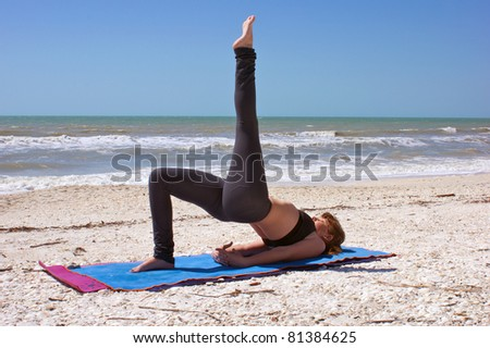 an athletic brown haired woman is doing yoga exercise one leg bridge pose on an empty beach at the gulf of mexico in bonita springs florida