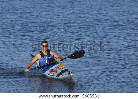 An athletic man is showing off his kayaking skills in calm waters of Mission Bay, San Diego, California. - stock photo
