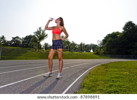 An athletic teenager exercising on a track outdoors