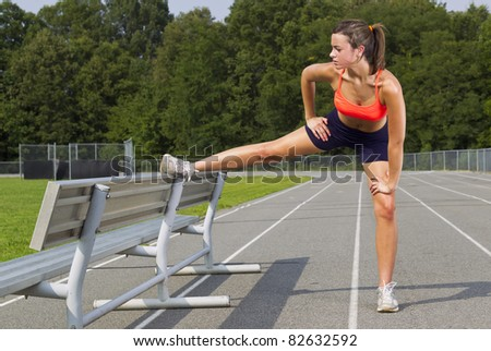 An athletic teenager stretching before exercising on a track outdoors