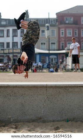 "An athletic young Briton engages in his passion for ""parkour"" or ""free running"" on the seafront at Great Yarmouth. The blurred figure on the right is also model released."