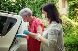 An attentive caregiver helps her elderly client to get into a car to travel for regular medical appointments. Both wear protective masks.