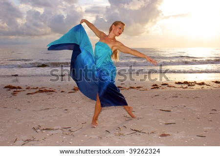 An attractive adult woman is dancing on the beach with the sun behind her and two seagulls in the background, she appears to be carefree.