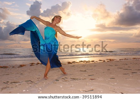 An attractive adult woman is dancing on the beach with the sun behind her , she appears to be happy and carefree.