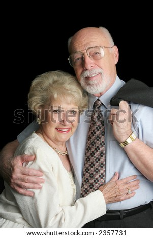 An attractive, affectionate senior couple on a black background.