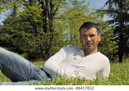 An attractive and cheerful man lying in the park