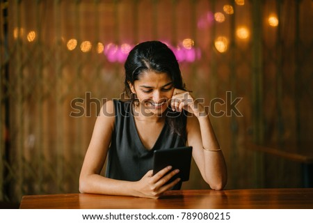 An attractive and young Indian woman in a black blouse is casually relaxing and reading a tablet e reader (e.g. a Kindle) at a wood table in a warm, cosy setting.