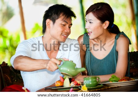 An attractive asian couple eating together at a restaurant