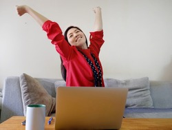 An attractive Asian woman working from home, smiling and stretching her arms, feeling happy after completing her tasks.