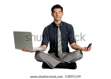 An attractive athletic businessman doing a yoga pose while using his mobile phone and laptop against white background