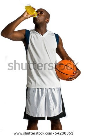 An attractive athletic man with a basketball drinking an energy drink against white background