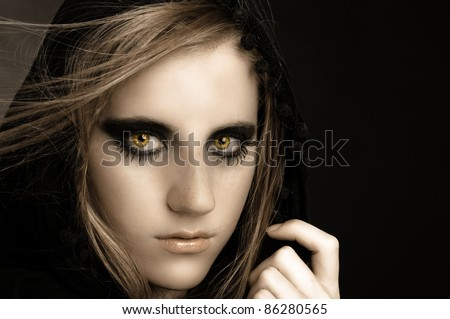 An attractive beautiful girl in hood against black background