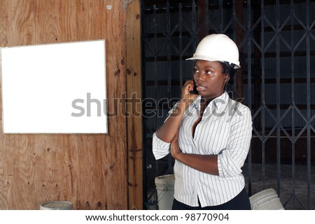 An attractive black woman wearing a white hardhat talks on her cell phone.  Beside and behind her is a white board on the wall where you can place your text or graphics.