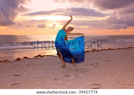 an attractive blonde female dancer on the beach at sunset in pose that makes her look like an artist's muse.