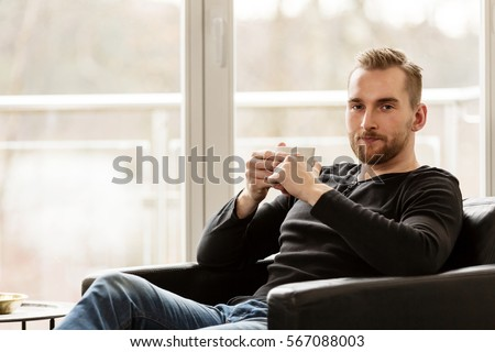 An attractive blonde man sitting down relaxing in his lounge chair holding a mug and looking at camera. Big bright large windows behind him.