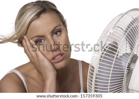 An attractive blonde woman with a deep tan cools off in front of an electric fan in hot weather