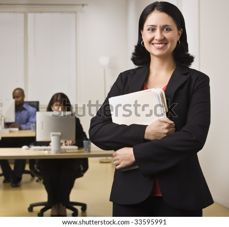 An attractive brunette is holding file folders and is smiling at the camera. There are people working on computers at the desks behind her.  Square composition.