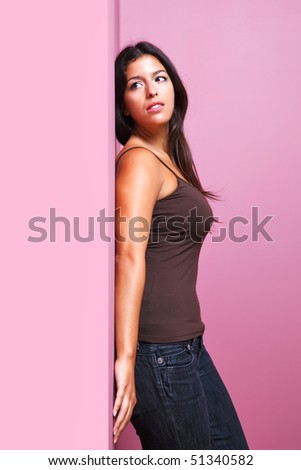 An attractive brunette woman in casual clothing leaning with her back against a wall in the corner of a room. Possible uses could include romance or listening related themes.