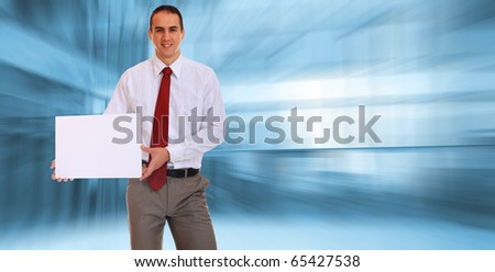 An attractive business man holding a white add in a light business environment