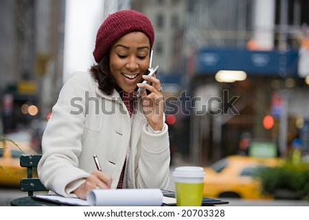 An attractive business woman talking on her cell phone while seated outdoors in the city.