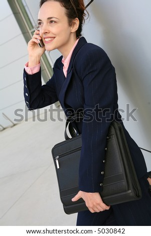 An attractive business woman talking on the phone outside her office