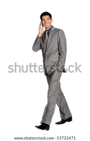 An attractive businessman using his mobile phone while standing against white background