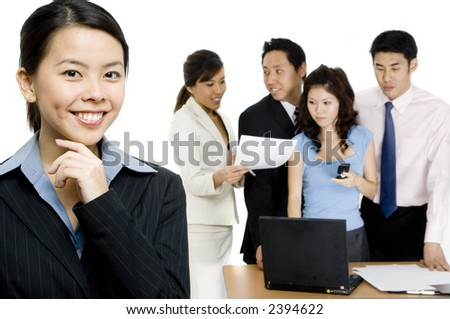 An attractive businesswoman standing in front of a busy working group