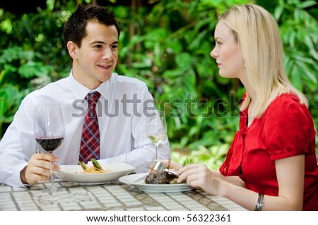 An attractive caucasian couple having a meal with wine at an outdoor restaurant