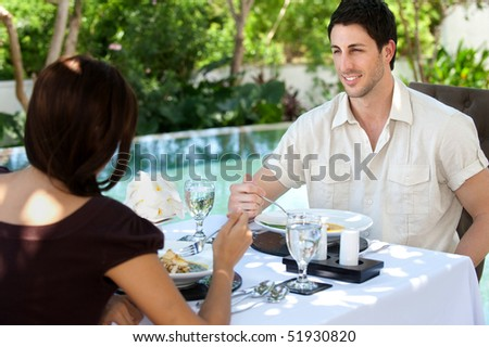 An attractive caucasian couple having a relaxing meal outdoors together