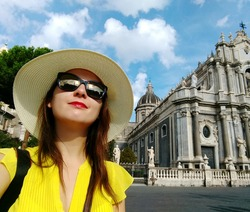 An attractive Caucasian female taking selfies with Cattedrale di Sant'Agata in the background