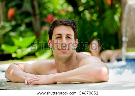 An attractive caucasian man relaxing in a jacuzzi pool outdoors