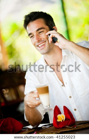 An attractive caucasian man with a drink and using his phone in a restaurant
