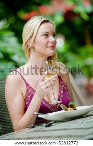 An attractive caucasian woman having a meal at an outdoor restaurant