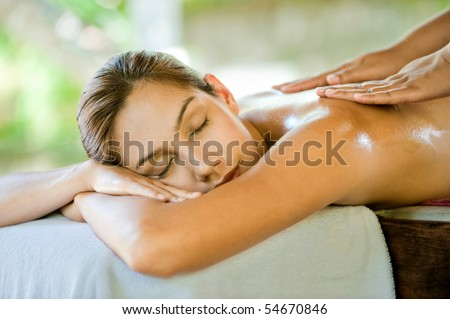 An attractive caucasian woman lying down on a massage bed at a spa - stock photo