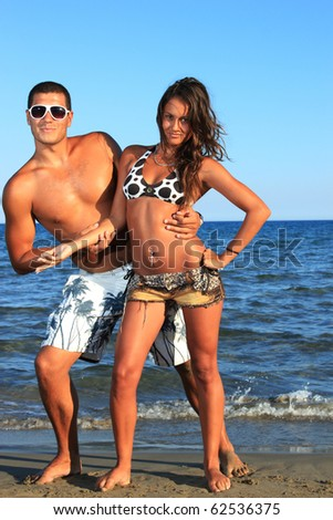 An attractive couple relaxing at the beach, at sunset