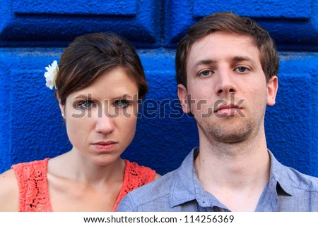 An attractive couple seriously looking in front of a blue wall
