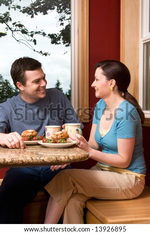 An attractive couple talking over breakfast by a large window, with a picturesque background, at home.  Vertically framed shot.