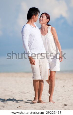 An attractive couple walking together on the beach