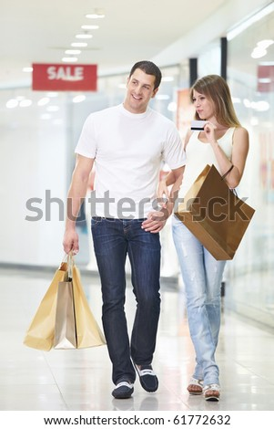 An attractive couple with a credit card at the store