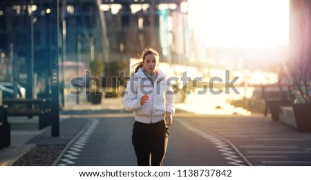 An attractive, determined female running outdoor in the city; training, preparing, jogging.  #1138737842