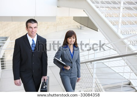 An attractive, diverse business man and woman team on stairs at office building