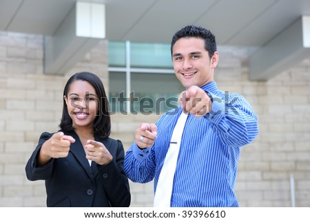An attractive, diverse business team at the office building pointing